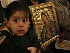 boy with a picture of our lady guadalupe